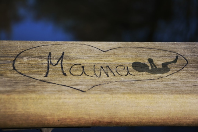 "Heart etched into wood with the word ""Mama"" and a silhouette of a baby in the womb"
